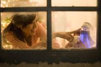 窓辺で人形に触れている女性