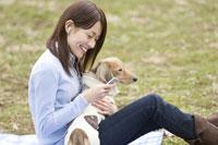 携帯音楽を聴く女性と犬