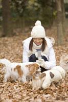 携帯電話を持つ女性と犬