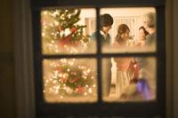 窓越しに見えるクリスマスの飾りと家族