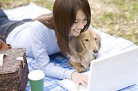 パソコンを使う女性と犬