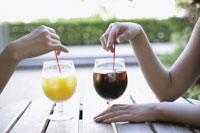 テラスで飲み物を飲む2人の女性