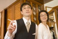 タバコを吸うビジネスマンとその妻
