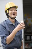 缶飲料を飲む作業員