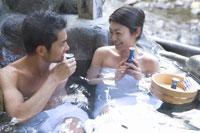 温泉に入りお酒を飲むカップル