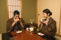 旅館の部屋でお茶を飲むカップル