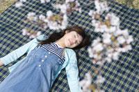 桜の花と寝転ぶ女性