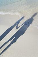 波打ち際に映るカップルの影