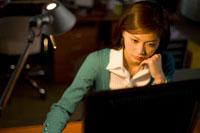深夜にパソコンへ向かう女性