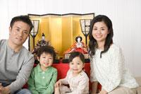 ひな人形の前に座った家族