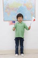 世界地図の前でアメリカと日本の旗を振る男の子