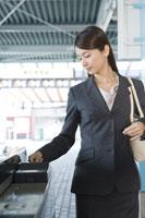 駅の改札を通過する女性