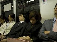 電車内で居眠りをするサラリーマンとOL