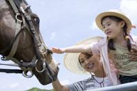 馬をなでる女の子と見守る母親