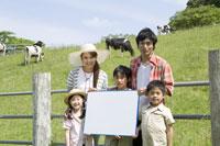 牧場の柵の前に立つ家族