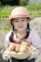 沢山の野菜を見せる女の子
