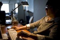 暗いオフィスでパソコンに向かう男性
