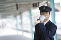 駅のホームでアナウンスをする駅員 28174009831| 写真素材・ストックフォト・画像・イラスト素材|アマナイメージズ