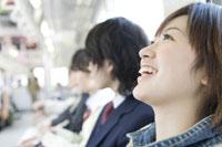電車の座席に座って笑顔を見せる女性