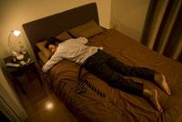 スーツを着たままベッドで眠るビジネスマン