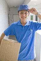 段ボール箱を持つ宅配便屋の男性