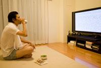 缶ビールを飲みながらテレビを見る男性