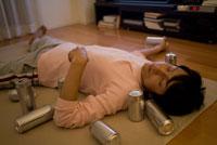 缶に囲まれて床で眠る男性