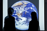 スクリーンに投影された地球の前に立つ男女