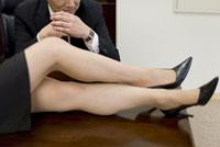 机の上に乗った女性の足を見る男性 28174010728| 写真素材・ストックフォト・画像・イラスト素材|アマナイメージズ