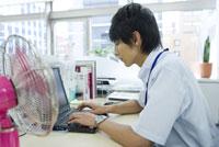 扇風機のあるデスクでパソコンをする男性