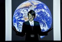 地球の投影されたスクリーンの前に立つ男性