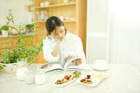 オレガノの鉢植えとハーブ本を読む女性