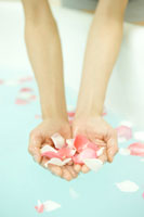 バスタブに浮かべたバラの花びらと女性の手