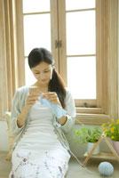 チャービルと花を置いた窓際で編み物をする女性