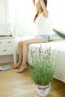 ベットサイドに置いたラベンダーと伸びをする女性 28177003029| 写真素材・ストックフォト・画像・イラスト素材|アマナイメージズ