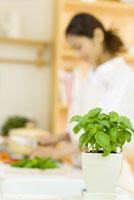スイートバジルのあるキッチンで料理をする女性