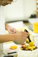 ケーキのデコレーションフルーツを仕上げるパティシエ