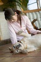 女性と寝転がる犬