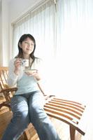 椅子に座ってカップを持つ女性 28182000498| 写真素材・ストックフォト・画像・イラスト素材|アマナイメージズ
