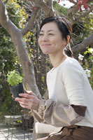植物を持っている笑顔の女性