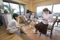 ティータイムをする三人の女性と犬