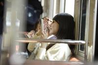 電車内で化粧を直す高校生