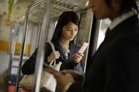 電車内で携帯電話を見ているOL