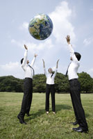 地球ボールを投げ上げるビジネスマンたち