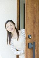 玄関から顔を出す笑顔の女性