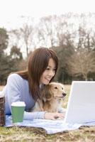 パソコンを操作する女性と犬