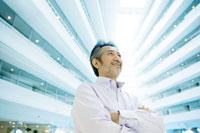 建物に囲まれた中で笑顔の男性