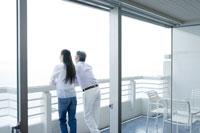 部屋のベランダから外の景色を眺める夫婦