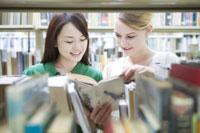 図書室で本を見るふたりの女子学生