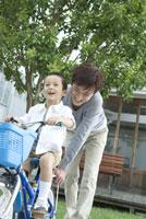 父親と自転車に乗る練習をする男の子